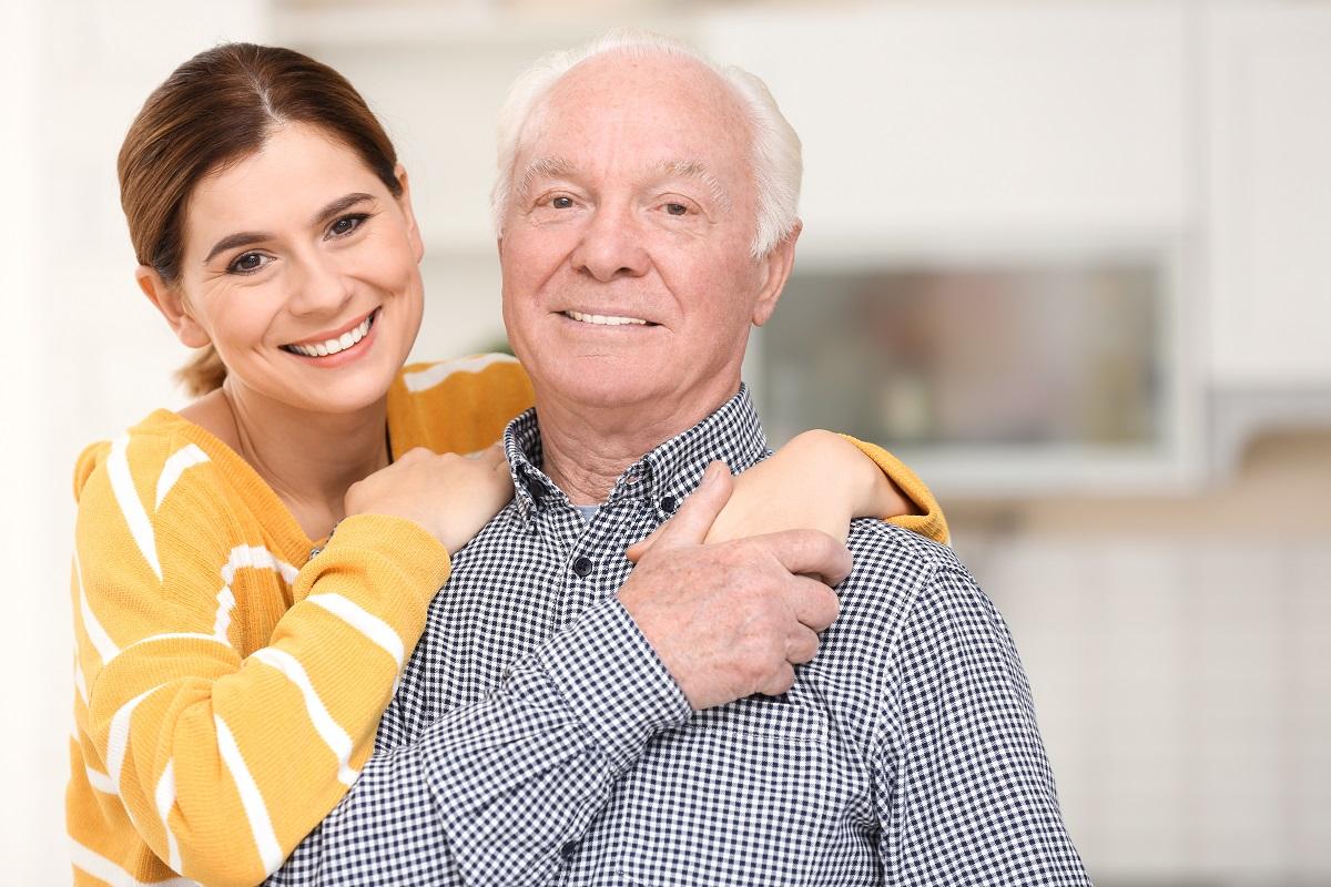 Elderly man with female caregiver in kitchen